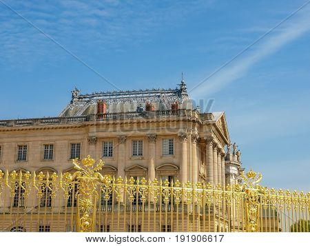 View of the part of a north wing of the Palace of Versailles across his gilding fence on the background of the sky France