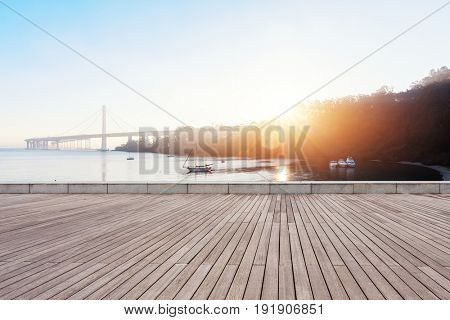 empty wooden floor near golden gate bridge at sunrise