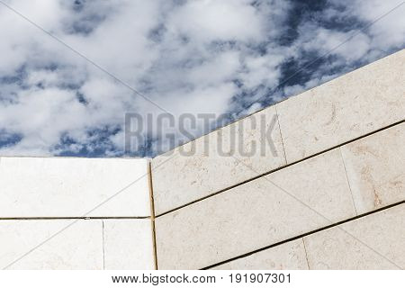 Cloudy sky above the concrete wall of an industrial building.
