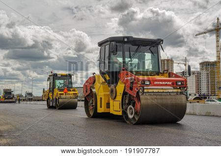 Tyumen, Russia - June 1, 2017: JSC Mostostroy-11. Construction of two-level outcome on bypass road on Fedyuninskogo and Permyakova streets intersection. Road roller compressing sand to highway construction
