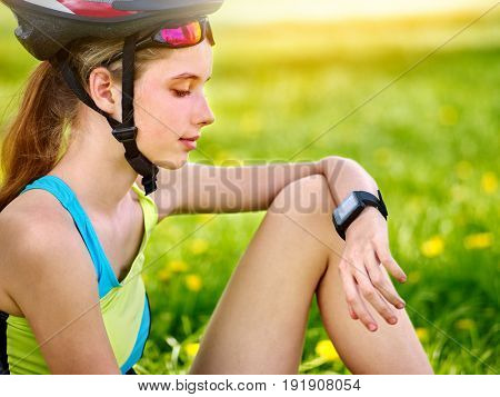 Woman traveling bicycle in summer park. Bicyclist girl watch on smart watch. Girl counts pulse after sport training. Kid is resting on nature at weekend. Sportswoman waiting for her friends.