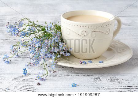 Forget me nots flowers in cup on table