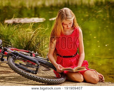 Girl in cycling reading book near bicycle into park outdoor. Cyclist looking at textbook. Schoolgirl does homework in nature. Without the internet education concepts.