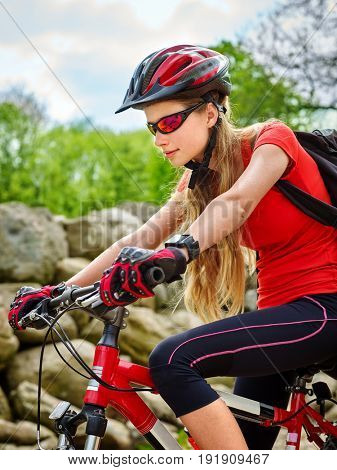 Woman on bicycle ride mountain. Girl traveling in summer park. Early morning with blue sky and clouds. Cycling person with rucksack. Sport trip is good for health. Healthy active lifestyle.