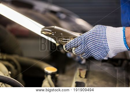 car service, repair, maintenance and people concept - auto mechanic man with lamp and pliers working at workshop