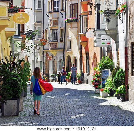 HALL AUSTRIA - JUNE 15: Undefined young woman goes shopping in the street of Hall on June 15 2014. Hall is a town located in northern Tyrol Austria.