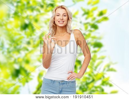 gesture, summer and people concept - happy smiling young woman in white top and jeans showing ok hand sigh over green natural background