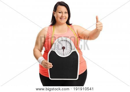 Overweight woman holding a weight scale and making a thumb up sign isolated on white background