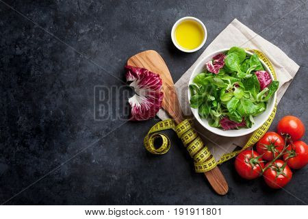 Healthy salad bowl on stone table. Top view with copy space