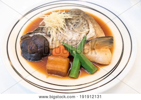 Boiled salmon head in sweet soy sauce served with carrot mushrooms okra radishes and ginger in a Japanese restaurant.
