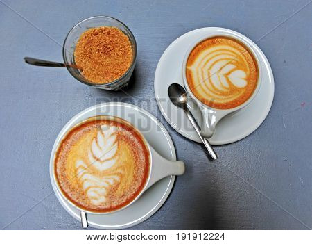 Cups of cappucino and latte on the wooden table