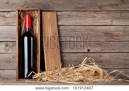 Red wine bottle in box in front of wooden wall. With copy space
