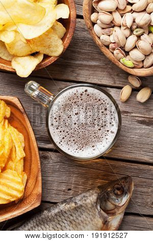 Lager beer mug and snacks on wooden table. Nuts, chips, dry fish. Top view