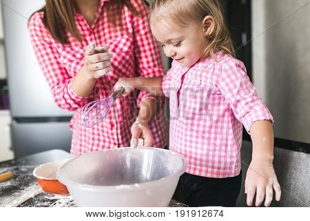Mom and little daughter in the kitchen play together with flour