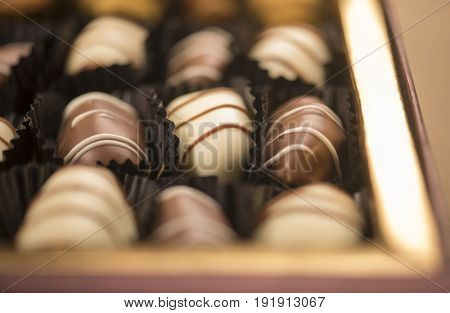 Finest quality date chocolates in a gift box. An extreme close up with out of focus treatment.