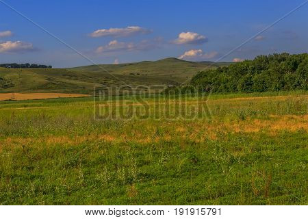 The overgrown field in the foothills against the background of the peaked hill over which white clouds. Krasnodar Krai Kuban Russia.