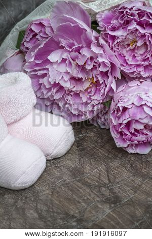 One pair of bootees for newborn girl with several peonies as background