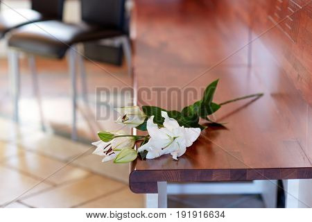 funeral and mourning concept - white lily on bench in church