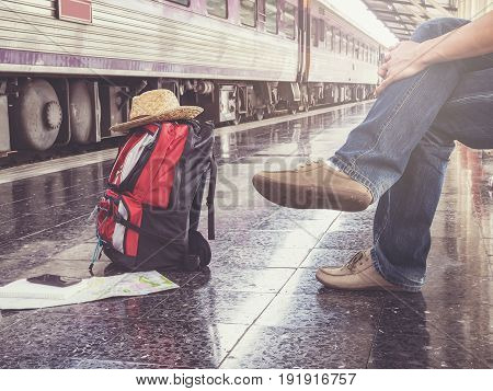 Traveler Sitting And Looking At The Map In Train Station. Travel Concept With Vintage Tone