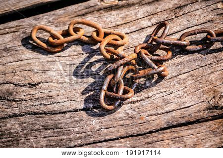 Rusty iron chain on a wooden background. Copy spase, space for text.