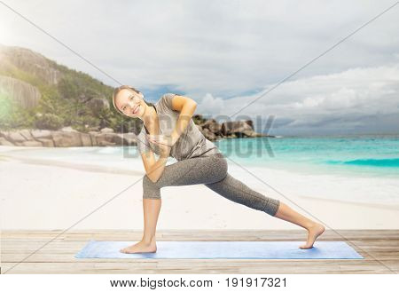 fitness, sport and people concept - happy smiling woman doing yoga side angle pose on mat over exotic tropical beach background