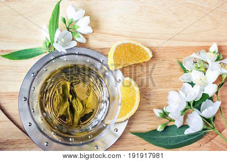 Cup of green tea with jasmine over light back. Beautiful composition. Top view of jasmine tea and jasmine flowers on wooden table with copy space.