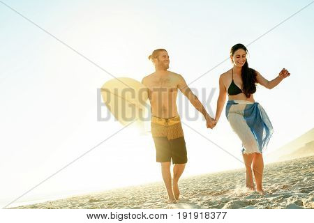 Smiling young couple in swimwear walking hand in hand with a surfboard together along a sandy beach on a sunny day