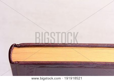 book with a gilt edge on the light grey background close-up view from above with space for your text