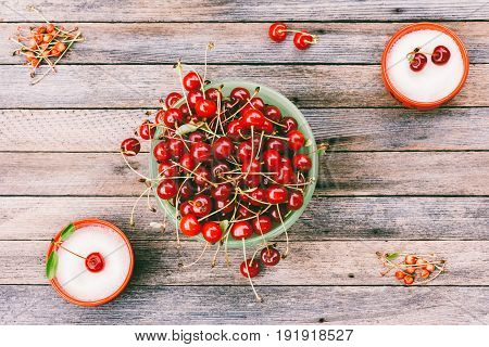 Green bowl with ripe cherry berries and cups with sugar on a wooden background top view toned photo