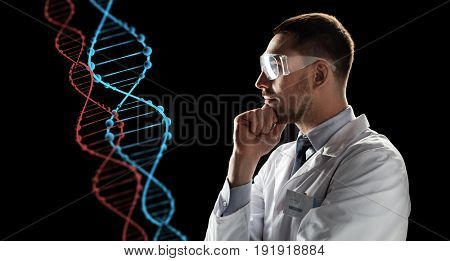 genetics, science and people concept - male doctor or scientist in white coat and safety glasses looking at virtual projection of dna molecule over black background