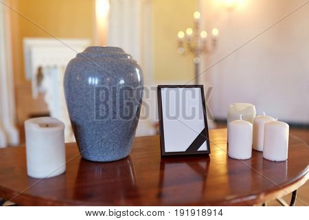 funeral and mourning concept - photo frame with black ribbon, cremation urn and candles on table in church