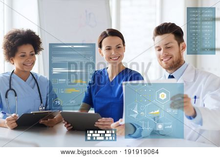 medicine, healthcare, technology and people concept- group of happy doctors with tablet pc computer and medical report meeting at medical office