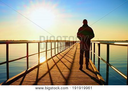 Man Silhouette Walk On Wharf Construction Above Sea To Sun. Fantastic Morning.