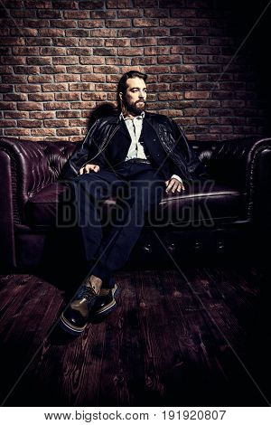 Portrait of a stylish handsome man on a leather sofa. Fashion shot. Men's clothing and accessories.