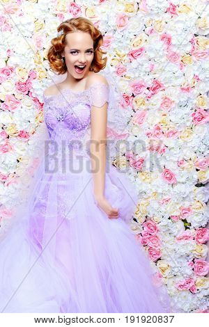Exciting bride woman in a beautiful dress posing by a background of roses. Wedding fashion.
