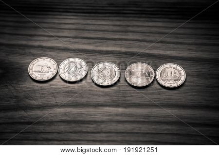 National anniversary Euro coins. Latvian currency on a wooden background