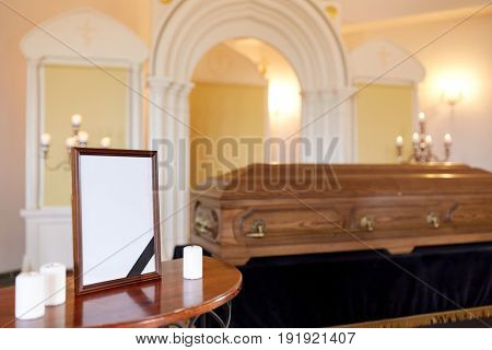 funeral and mourning concept - photo frame with black ribbon, candles and coffin at church