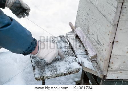 Beekeeper wearing warm clothes removing snow from a beehive outdoor cropped photo
