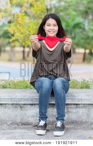 Asian woman hand hold beautiful red heart sweet loving symbol of take care or charity help to you.