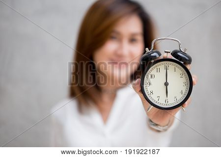 Asian Women Show Clock Times At 6 O'clock, It's Time To Do Something Concept