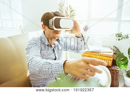 The man with glasses of virtual reality at home. Future technology concept.