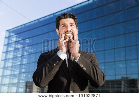 Arabic angry irritated aggressive tired businessman or worker in black suit with beard standing in front of an office glass building with hands on his face.