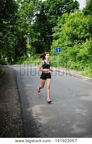 Sport Girl At Sportswear Running In A Green Park And Training At Nature. A Healthy Lifestyle.