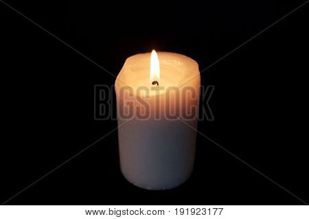 mourning and commemoration concept - candle burning in darkness over black background