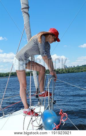 Sail boat yacht mooring. Beautiful girl in sailor suit on a yacht at summer day
