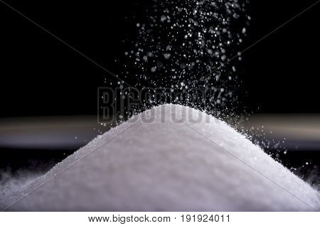 Close up shot of flowing sugar forming a pile as it falls