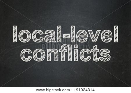 Political concept: text Local-level Conflicts on Black chalkboard background