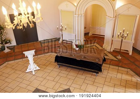 funeral and mourning concept - coffin with flowers and stand in church