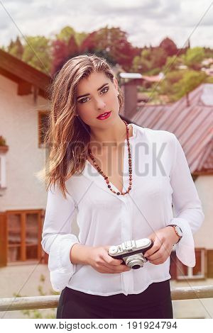 Portrait of a beautiful young playfully fashionable woman with old retro camera. Model looks into the camera