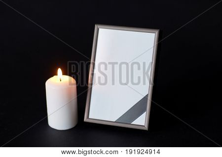 funeral and mourning concept - empty photo frame with ribbon and burning candle over black background
